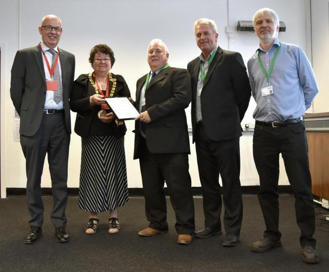 PRESENTATION: Mayor Hilary Harrington presents John Coughlan, of TSP Engineering, with the firm's ISO 19443 accreditation