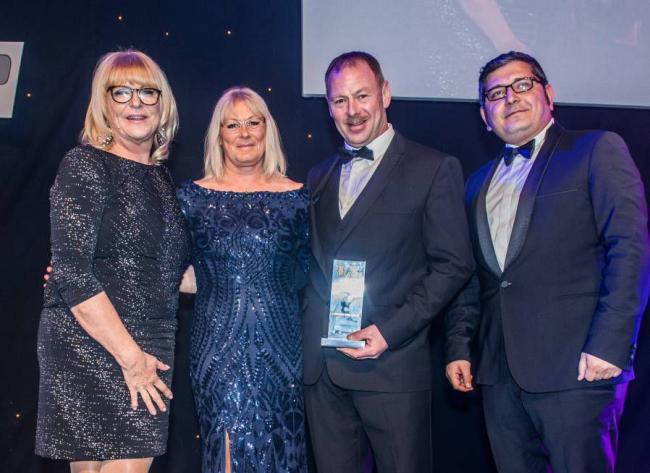 Collecting the first award of the night from Sally Traffic (left) and Mr Eray Gül, Area Sales Manager at Kässbohrer Fahrzeugwerke GmbH (right) - Raymond Lawson and Pauline Lawson (centre).
